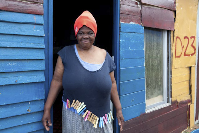 Black woman in front of blue-coloured shack